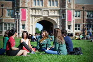 group of students sitting and talking on campus in-line