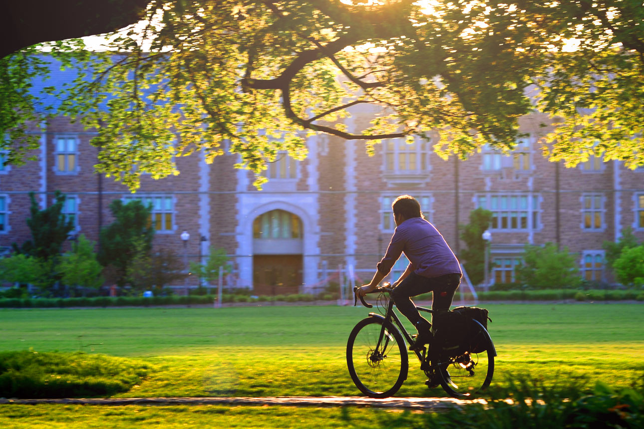 student riding bike on campus in-line